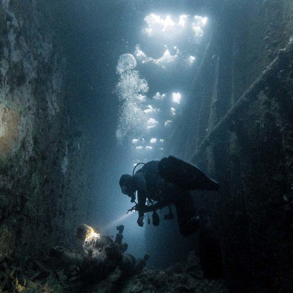 Dykker under vann inne i vrakt med dykkerlykt