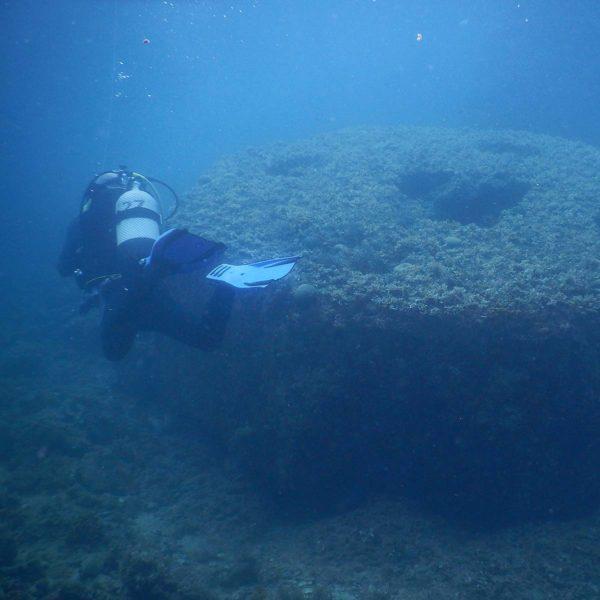 Dykker som dykker rundt en stor sirkelkonsktruksjon på bunn