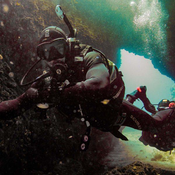 Dykkere som dykker inn en grotte