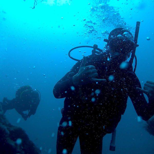 Dykkere under vann viser tegn at de er fornøyde