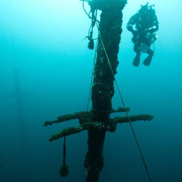 Dykker som dykker rundt masten på et skipsvrak