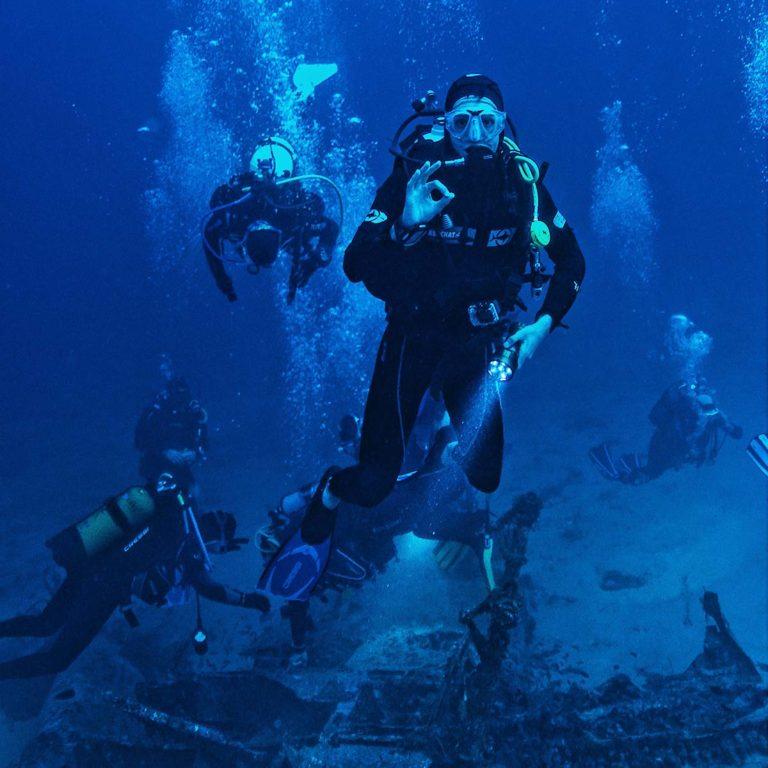 Vrakdykking under vann, blått hav med mange dykkere