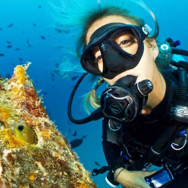 Dame som dykker under vann med små fisker
